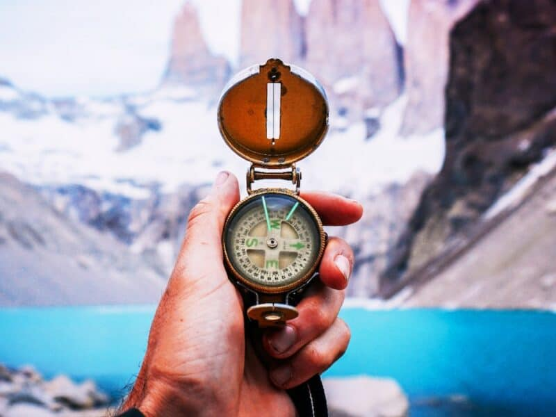 compass in hand snow mountains